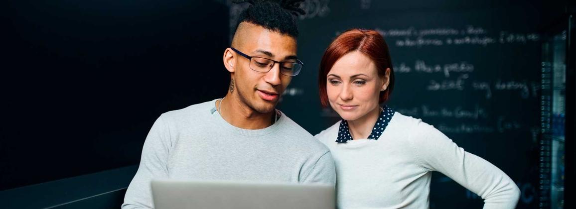 Dues persones conversen mirant un ordinador portàtil que sostenen amb les mans.