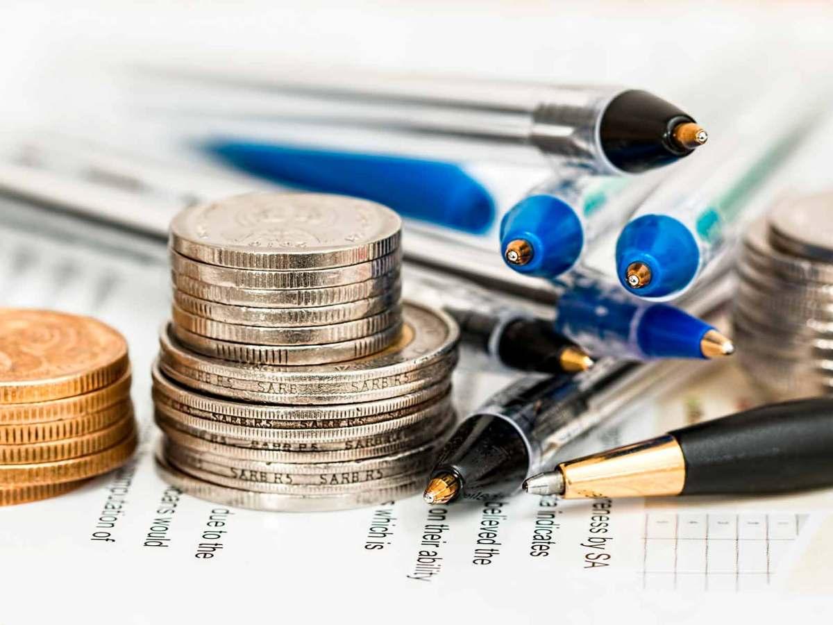 Una pila de monedes al costat d'uns quants bolígrafs sobre una fulla de càlcul.