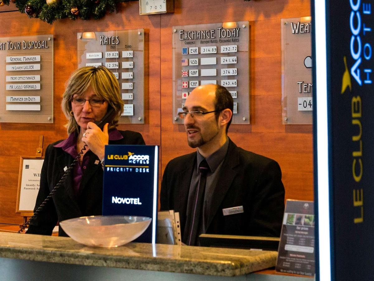 Recepció d'un hotel amb dos recepcionistes treballant.