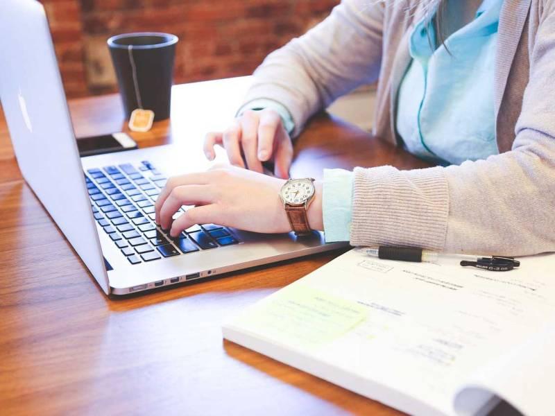 Una persona treballant amb un ordinador portàtil mentre pren una tassa de te.