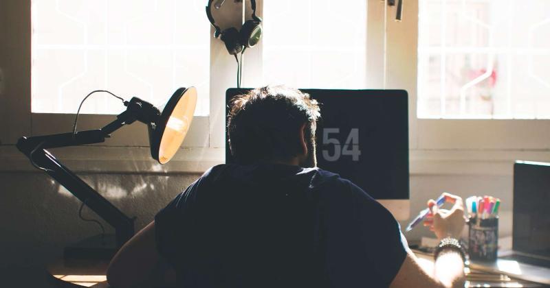 Persona treballant davant d'un ordinador.