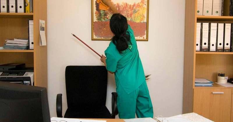 Una dona treballadora de la neteja passa un drap a un quadre d'un despatx.