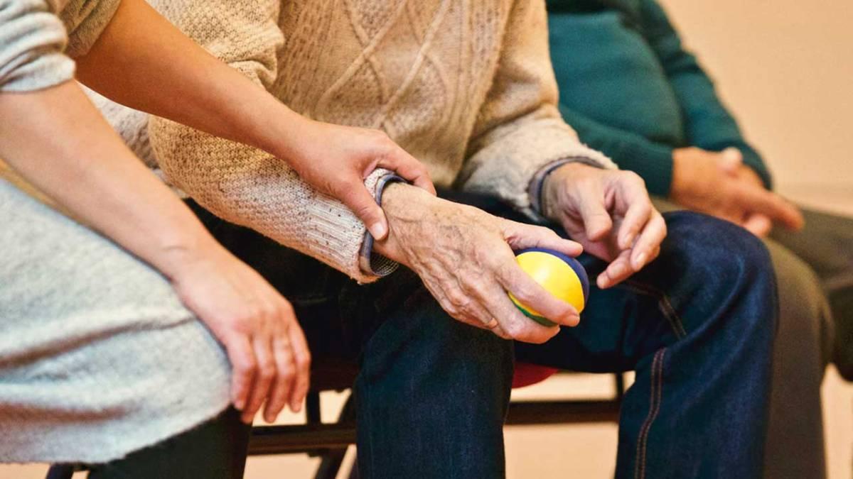 Una persona assistint a un home d'avançada edat.