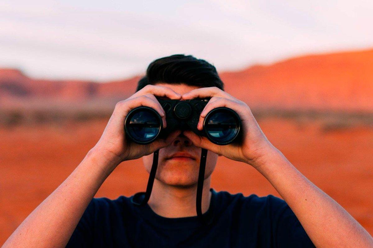 Un home mirant a través d'uns binoculars.