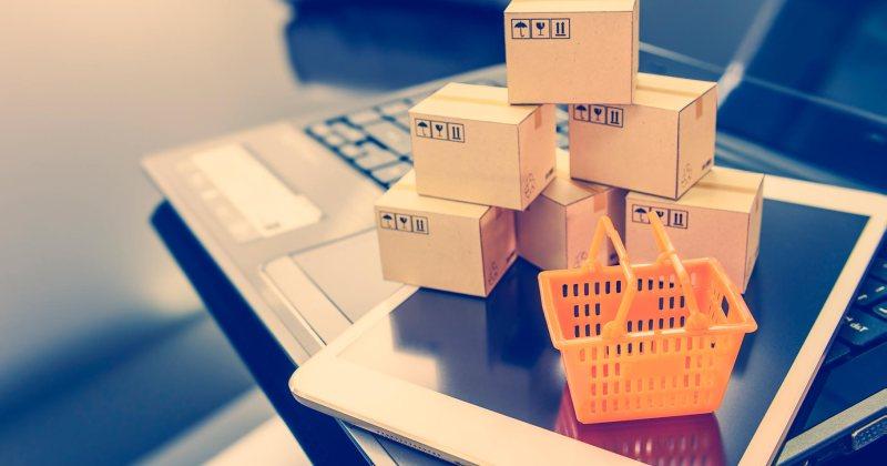 Unes capsetes de cartró petites sobre una tauleta i un ordinador. Alegoria del comerç electrònic.