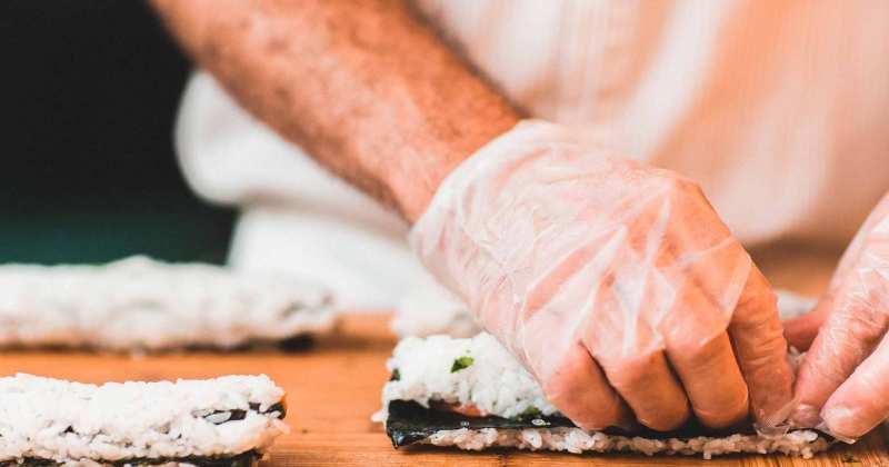 Una persona amb guants prepara sushi.