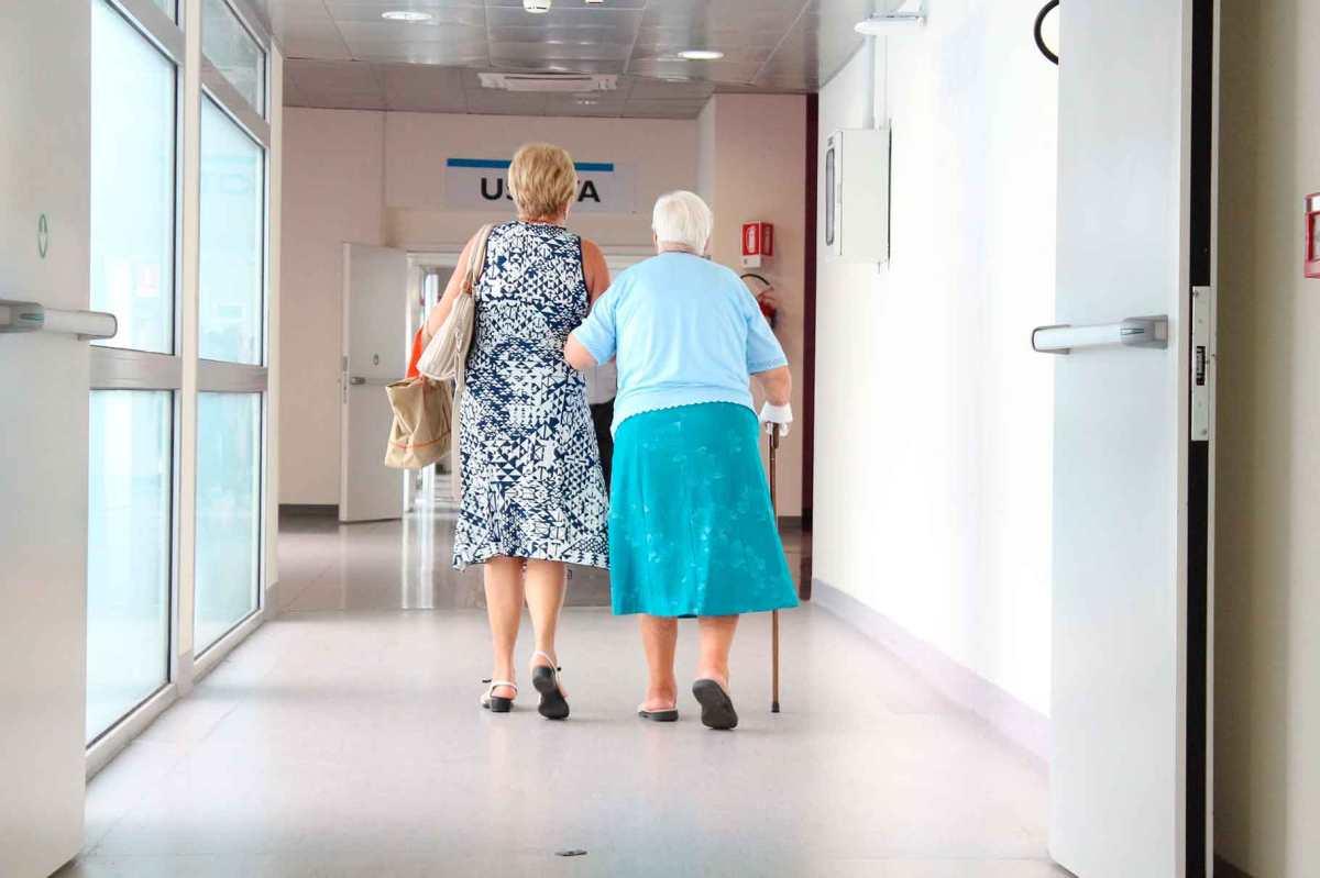 Una persona gran i la seva acompanyant caminen pel passadís d'un hospital.