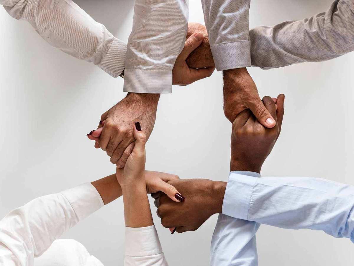 Quatre persones s'agafen de les mans ens un simbolitzant la cooperació.