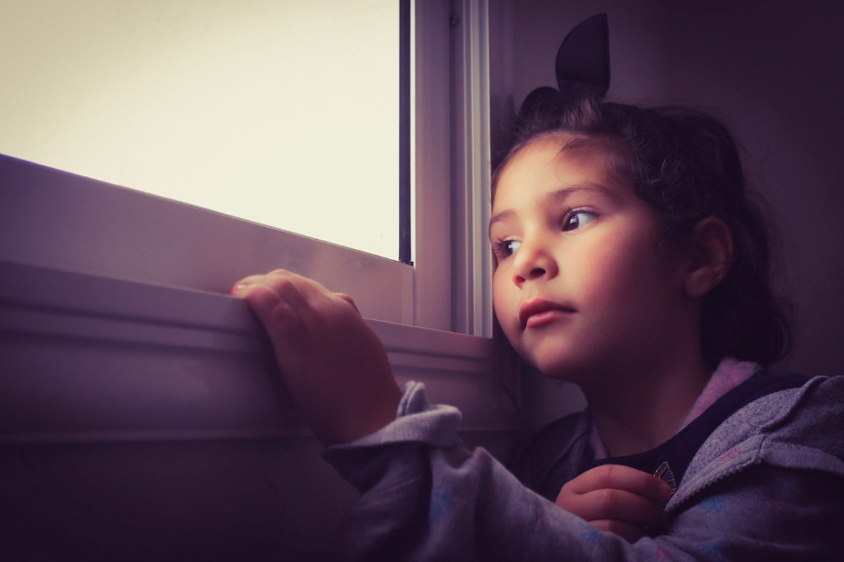Una nena a casa mira per la finestra.