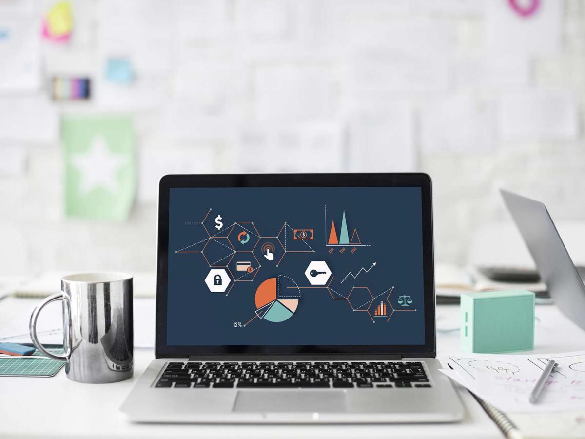Un ordinador portàtil a sobre d'una taula amb símbols i diagrames de dades a la pantalla.