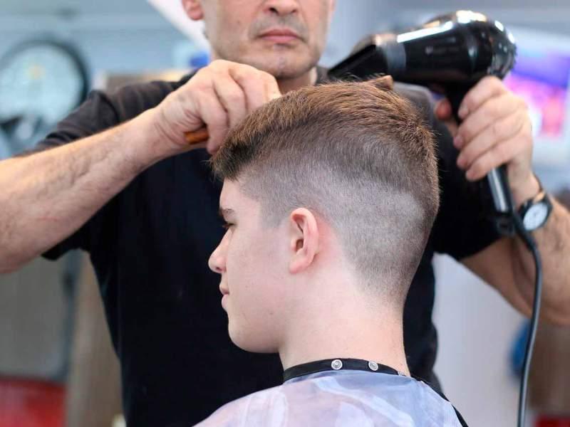 Un perruquer talla els cabells a un noi.