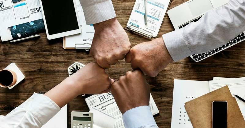 Quatre mans amb el puny tancat es toquen en senyal de cooperació i ajuda. Al fons, es veuen elements d'oficina (ordinador, telèfon mòbil, factures, calculadora, carpetes i documentació).