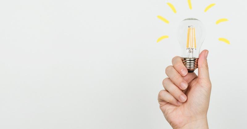Una mà subjectant una bombeta encesa com a símbol d'idea.