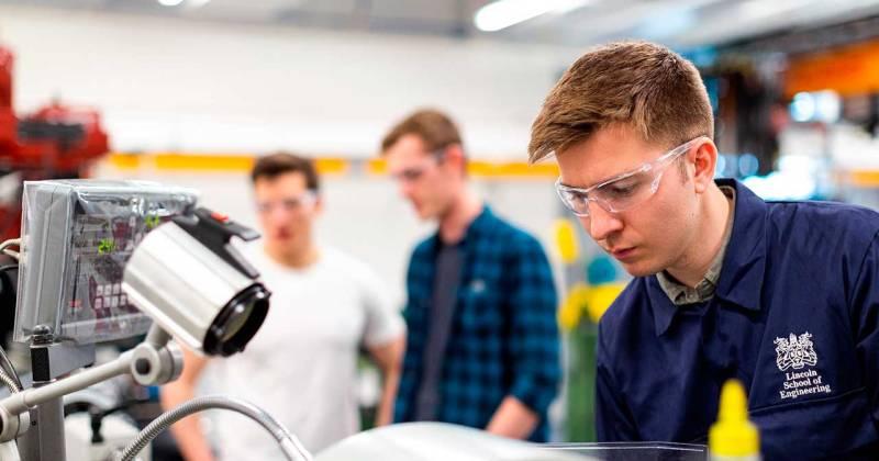 Un enginyer manipula un robot en un taller.