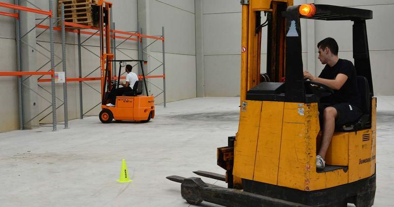 Dos operaris manipulen carretons de càrrega en una nau industrial.