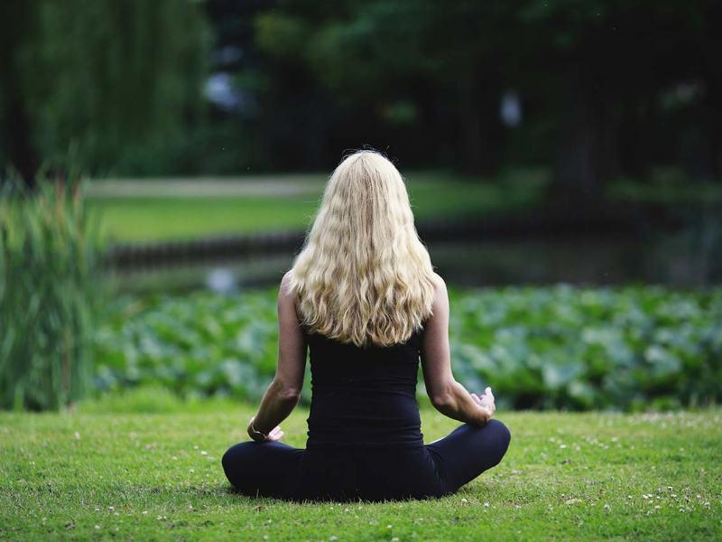 Una dona d'esquenes medita asseguda enmig d'un prat.
