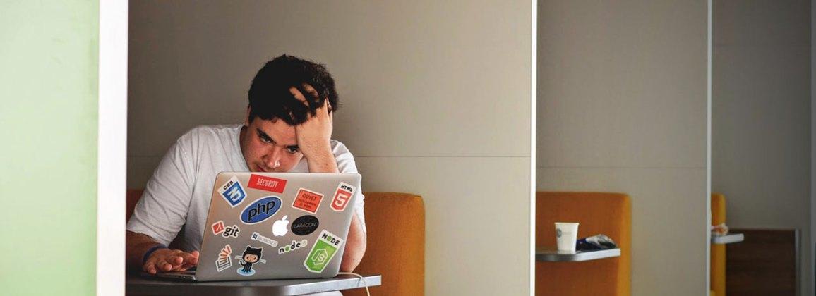 Un noi assegut a una cafeteria mira molt concentrat la pantalla d'un ordinador portàtil.