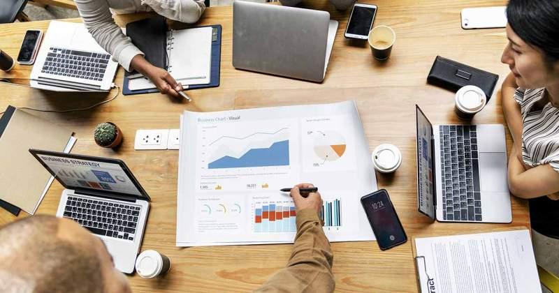 Quatre persones en una reunió d'empresa amb els seus ordinadors i documents sobre la taula.