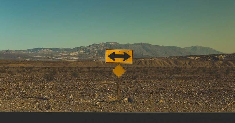 Una senyal enmig d'un paisatge que indica amb una fletxa cap a l'esquerra i cap a la dreta a la vegada.