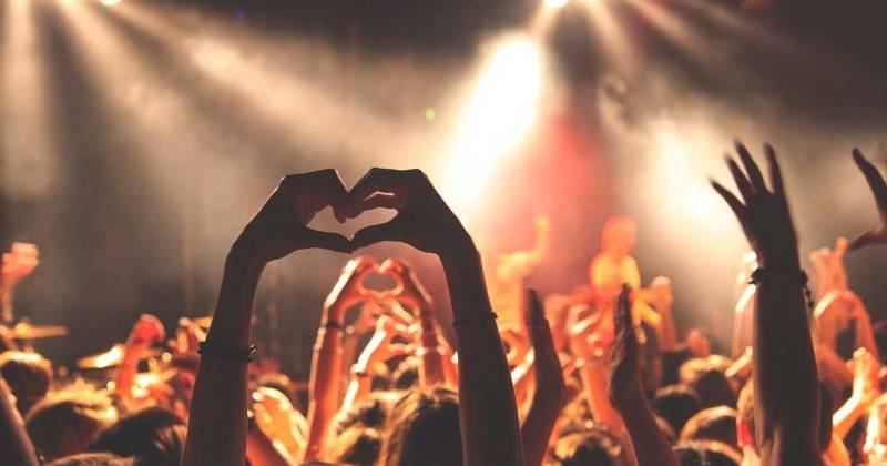 Persones amb les mans alçades ballant a un concert.