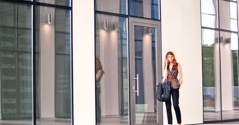 Una dona parla per telèfon dempeus davant la porta d'una edifici.