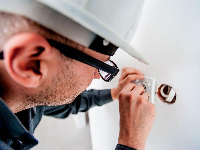 Un electricista arreglant un endoll mentre l'incrusta a la paret,