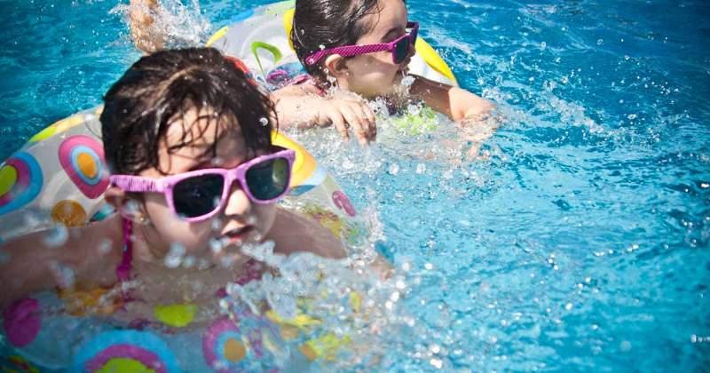 Dues nenes jugant en una piscina.