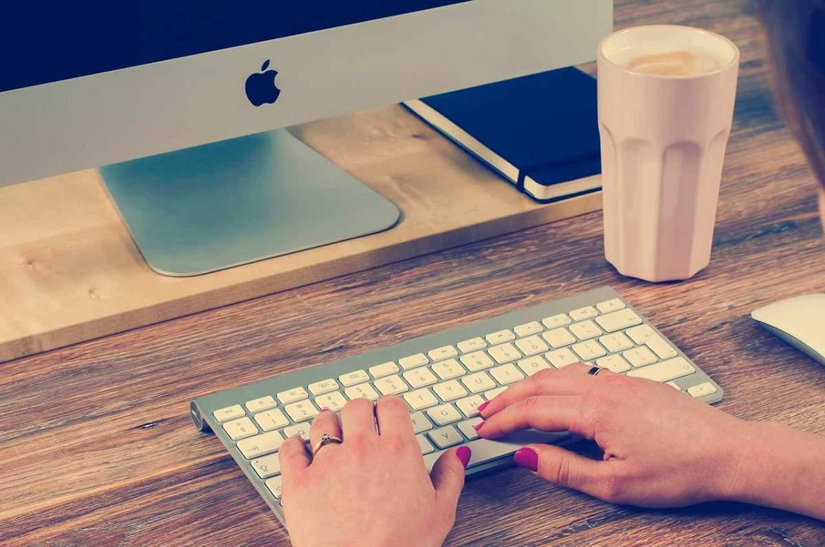 Mans amb les ungles pintades sobre un teclat.