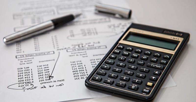 Una calculadora a sobre d'una taula enmig de papers de comptabilitat.