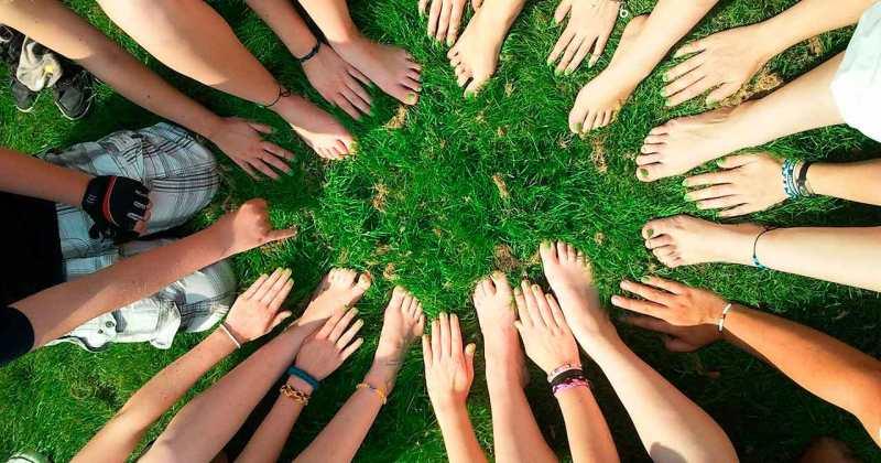 Mans i peus junts, formant una rotllana sobre la gespa.
