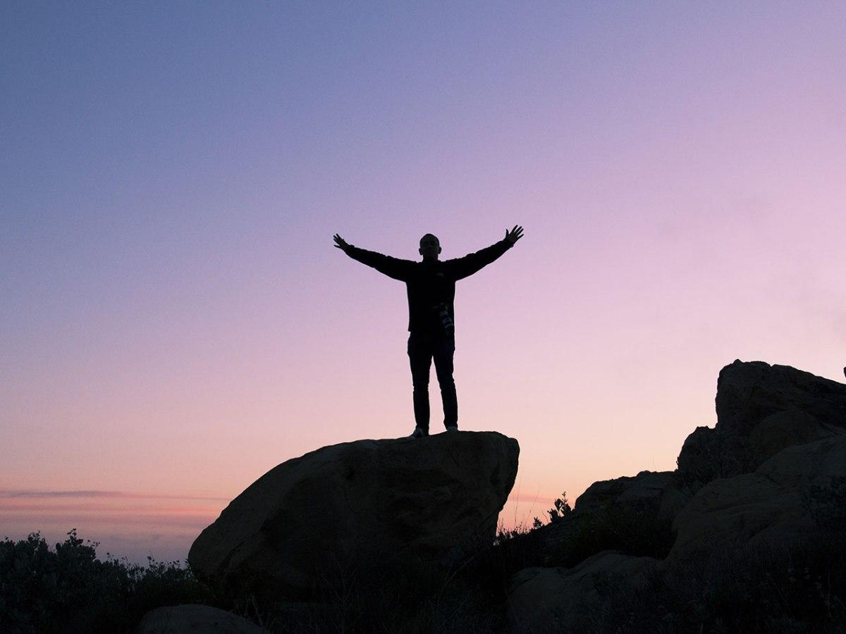 Silueta d'una persona sobre una obrint els braços cap a l'horitzó.
